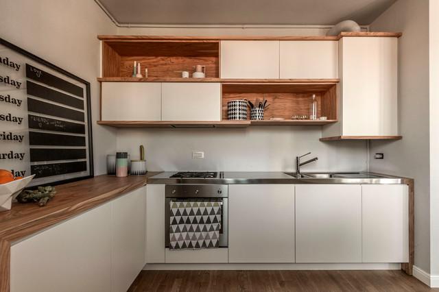 Exemple d'une cuisine moderne en L avec un évier intégré, un placard à porte plane, des portes de placard blanches, un plan de travail en inox, une crédence blanche, un électroménager en acier inoxydable et un sol en bois brun.