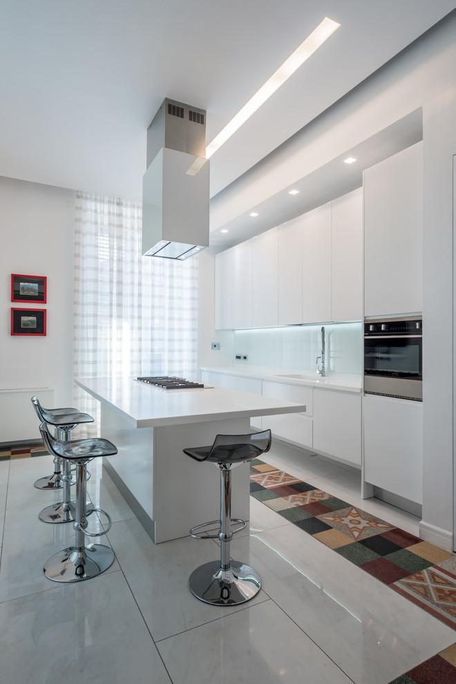 Immagine di una grande cucina contemporanea con ante lisce, ante bianche, paraspruzzi bianco, paraspruzzi con piastrelle in ceramica, elettrodomestici in acciaio inossidabile e isola