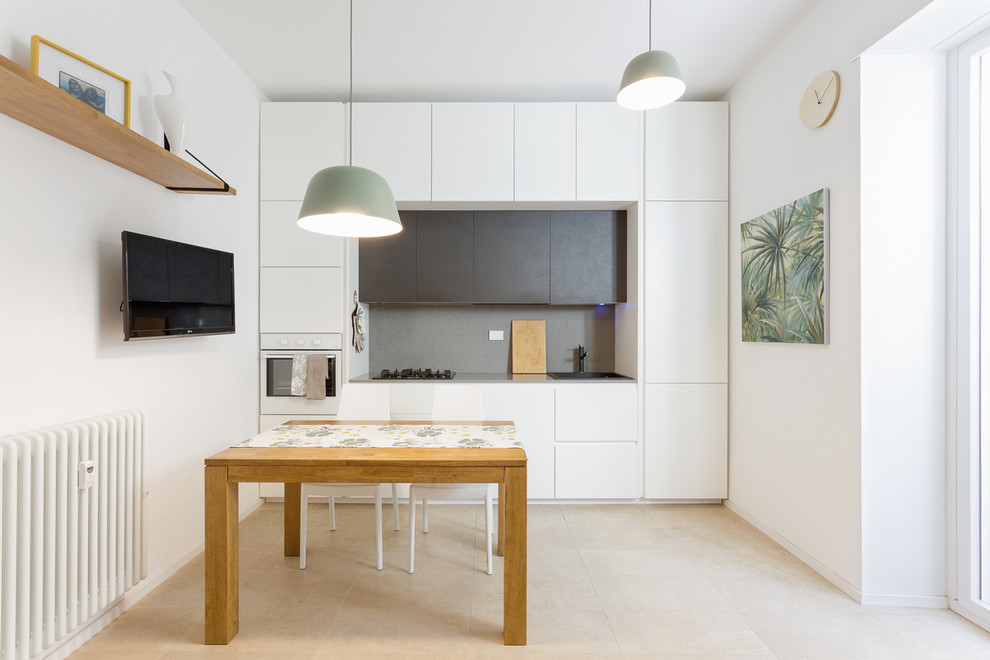 Example of a small trendy single-wall beige floor eat-in kitchen design in Rome with flat-panel cabinets, white cabinets, gray backsplash, no island, a drop-in sink and paneled appliances