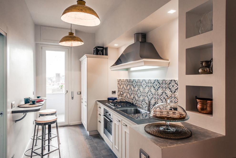 Esempio di una cucina lineare chic chiusa con lavello da incasso, ante con bugna sagomata, ante bianche e elettrodomestici in acciaio inossidabile
