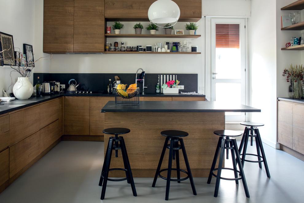 Foto di una cucina a L minimalista con ante lisce, ante in legno bruno, paraspruzzi nero e isola