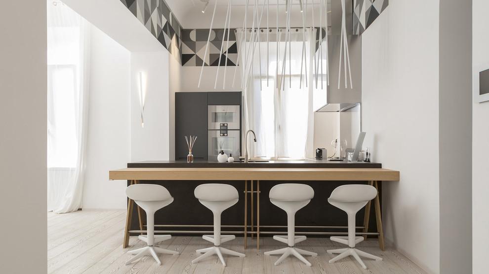 Esempio di una cucina parallela minimal con ante lisce, ante grigie, top in legno, elettrodomestici in acciaio inossidabile, penisola, pavimento beige e top beige