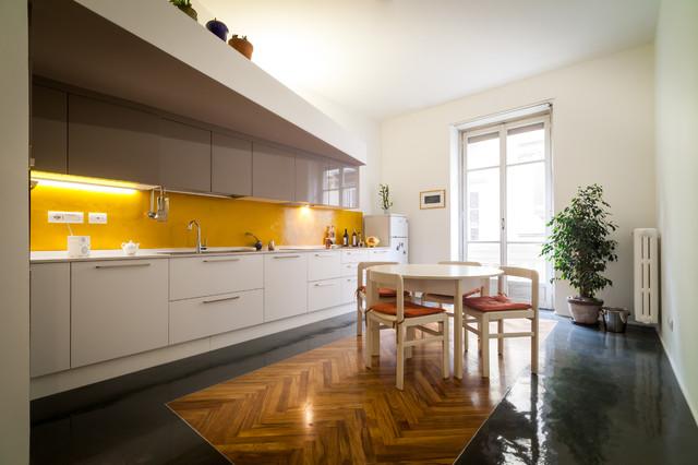 Idee per una grande cucina minimal con lavello sottopiano, ante lisce, ante bianche, paraspruzzi giallo e pavimento in gres porcellanato