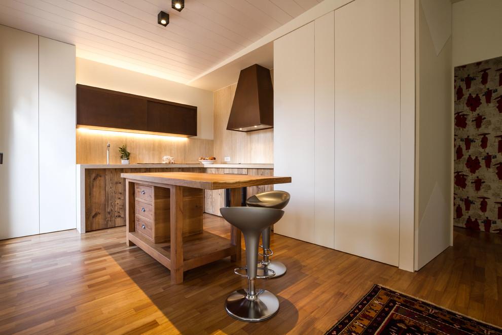 Immagine di una cucina a L mediterranea con ante lisce, ante in legno scuro, paraspruzzi beige, paraspruzzi in legno, pavimento in legno massello medio, isola e pavimento marrone