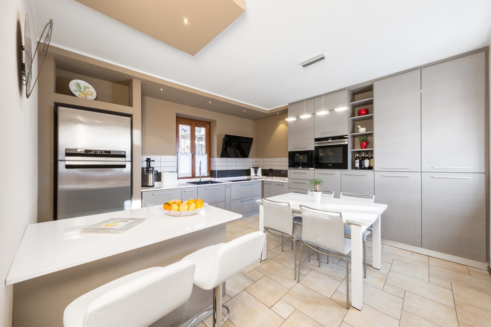 Example of a small trendy l-shaped eat-in kitchen design in Turin with a single-bowl sink, flat-panel cabinets, gray cabinets, white backsplash, stainless steel appliances and a peninsula