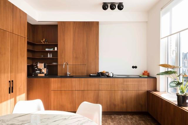 Ispirazione per una cucina design con ante in legno scuro, top nero, lavello sottopiano, ante lisce, paraspruzzi bianco, elettrodomestici da incasso, nessuna isola e pavimento marrone
