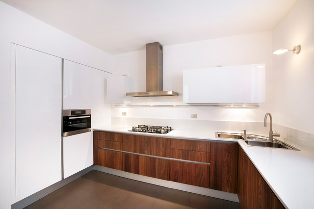 Kitchen - modern l-shaped kitchen idea in Milan with a drop-in sink, flat-panel cabinets, dark wood cabinets, white backsplash and stainless steel appliances