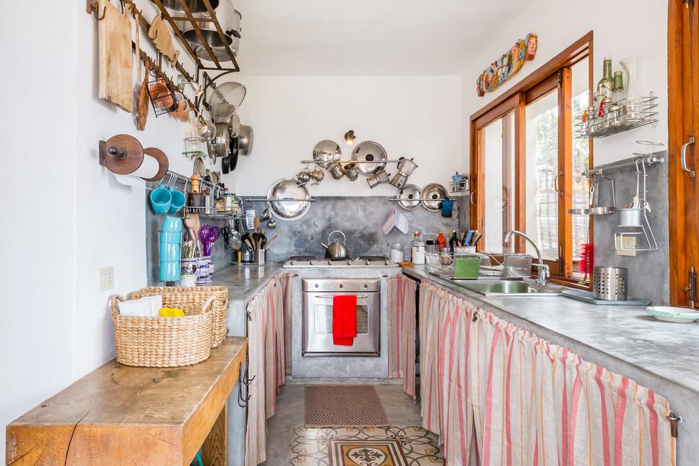 Immagine di una cucina a U mediterranea chiusa e di medie dimensioni con lavello da incasso, nessun'anta, top in cemento, paraspruzzi grigio, elettrodomestici in acciaio inossidabile, pavimento in cemento, pavimento grigio e nessuna isola