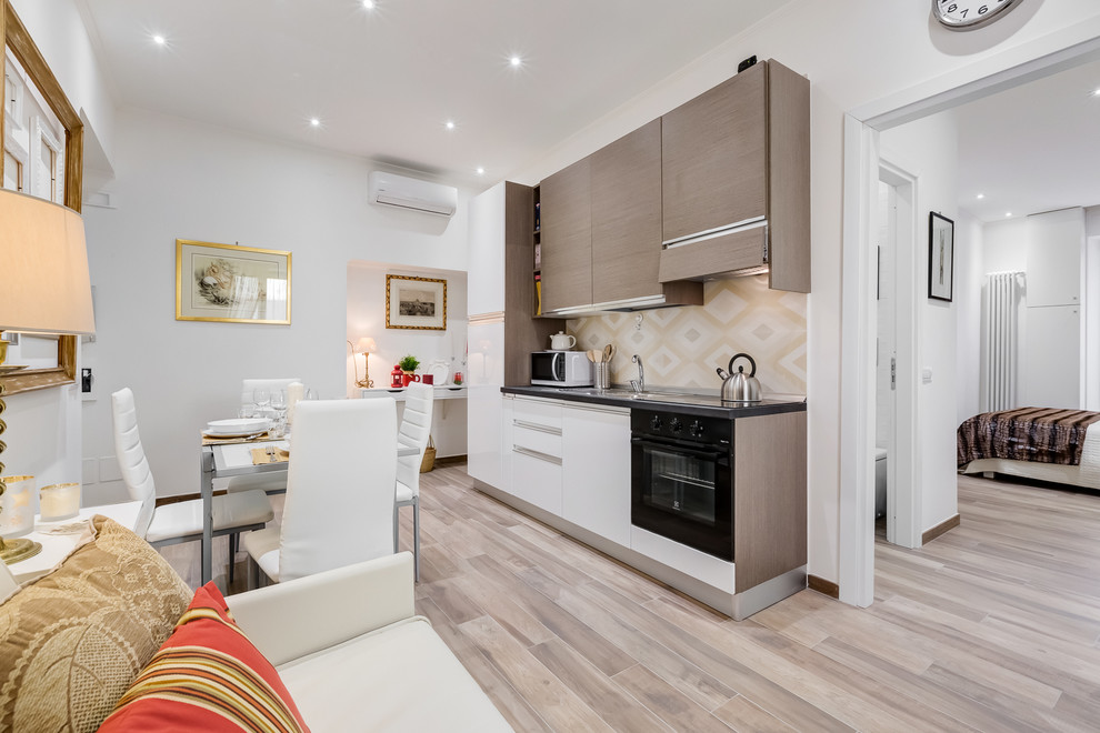 Example of a small trendy single-wall medium tone wood floor eat-in kitchen design in Rome with flat-panel cabinets