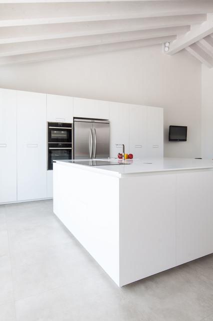 Esempio di una cucina minimalista di medie dimensioni con ante lisce, ante bianche, top in quarzo composito, elettrodomestici in acciaio inossidabile e isola