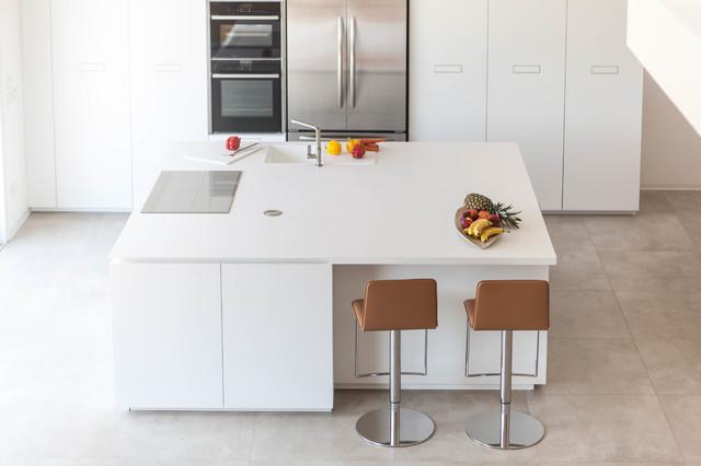 Foto di una cucina minimalista di medie dimensioni con ante lisce, ante bianche, top in quarzo composito, elettrodomestici in acciaio inossidabile e isola