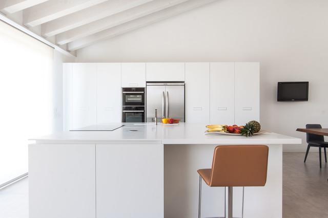 Immagine di una cucina moderna di medie dimensioni con ante lisce, ante bianche, top in quarzo composito, elettrodomestici in acciaio inossidabile e isola