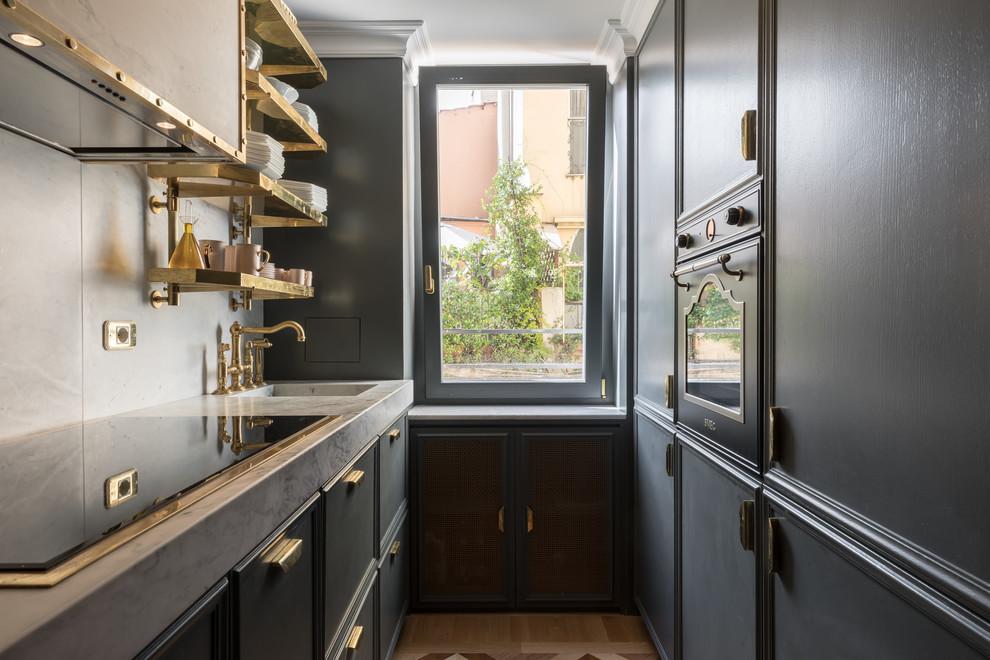 Foto di una cucina ad U tradizionale con lavello integrato, ante nere, paraspruzzi bianco, elettrodomestici neri, pavimento in legno massello medio, nessuna isola, pavimento marrone e top bianco