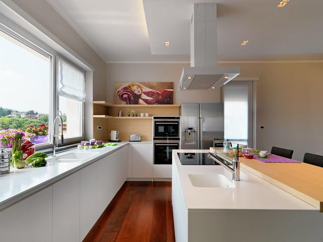 Inspiration för mellanstora moderna kök, med en integrerad diskho, släta luckor, vita skåp, glaspanel som stänkskydd, rostfria vitvaror, mellanmörkt trägolv och en köksö