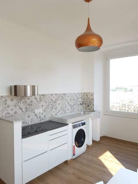 Immagine di una cucina minimal di medie dimensioni con ante lisce, ante bianche, top in laminato, paraspruzzi multicolore, paraspruzzi in gres porcellanato, pavimento in laminato e top nero
