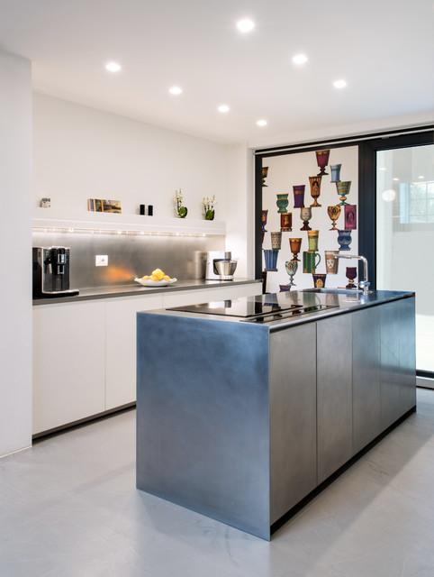 Ispirazione per una cucina parallela minimal di medie dimensioni con lavello integrato, ante lisce, ante in acciaio inossidabile, top in acciaio inossidabile, elettrodomestici in acciaio inossidabile, pavimento in cemento, isola, pavimento grigio, paraspruzzi grigio e top grigio