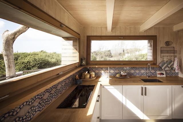 Foto di una cucina a L costiera di medie dimensioni con lavello sottopiano, ante con bugna sagomata, ante bianche, top in legno, paraspruzzi multicolore e paraspruzzi con piastrelle in ceramica