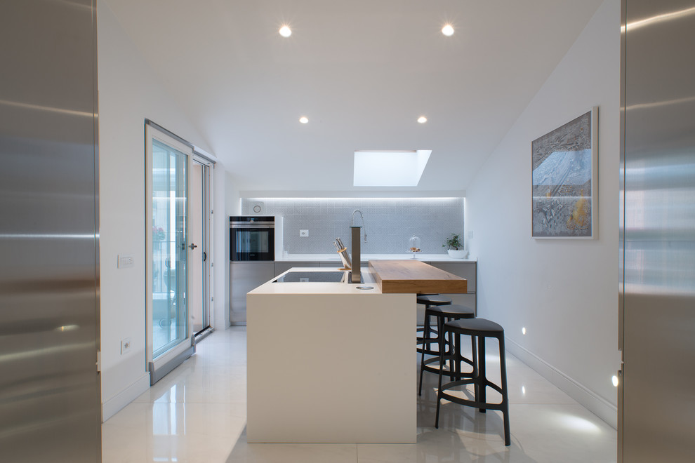 Inspiration for a mid-sized contemporary porcelain tile open concept kitchen remodel in Naples with a single-bowl sink, flat-panel cabinets, stainless steel cabinets, gray backsplash, an island, ceramic backsplash and stainless steel appliances