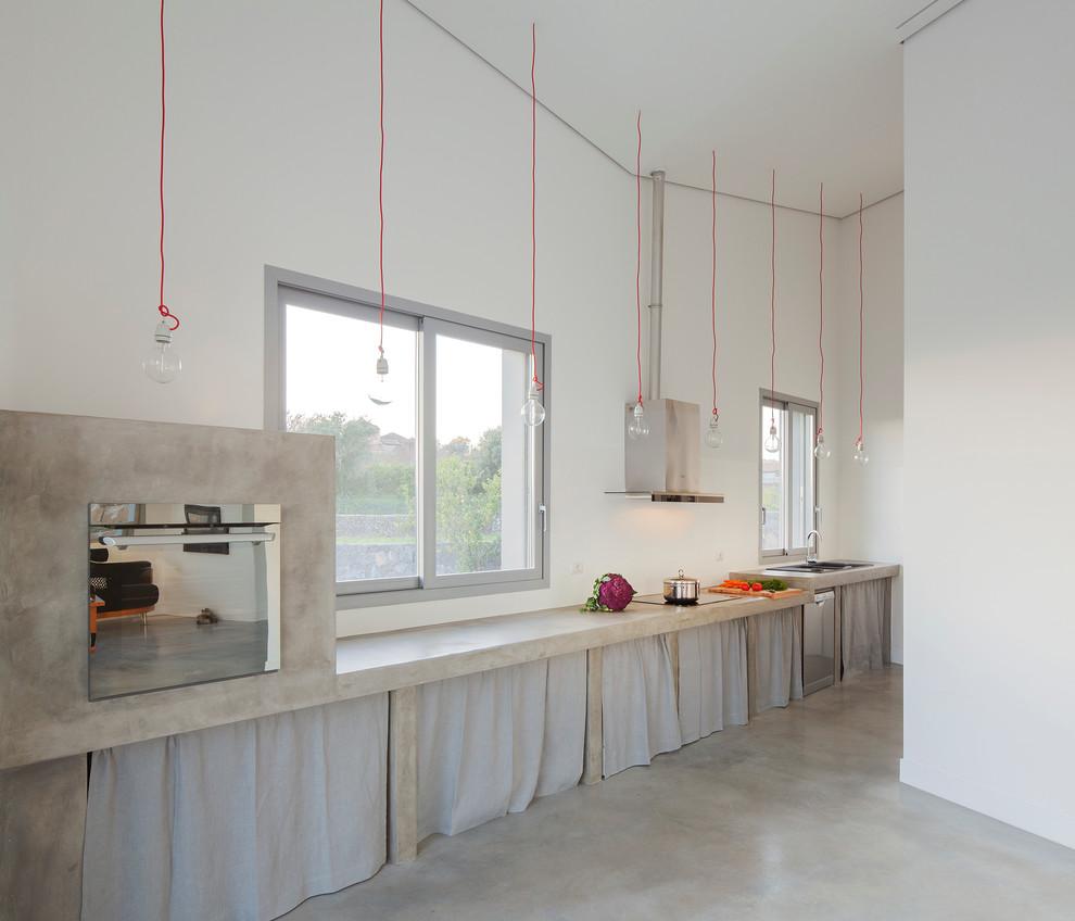 Foto di una cucina contemporanea con nessun'anta, ante grigie, top in cemento, elettrodomestici in acciaio inossidabile e pavimento in cemento