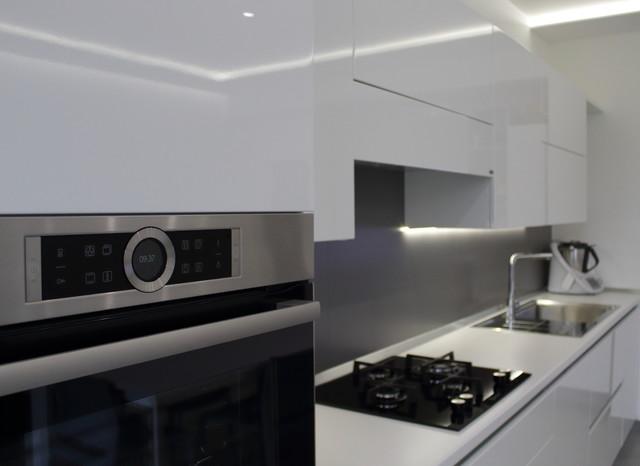 Foto di una cucina design di medie dimensioni con lavello da incasso, ante lisce, ante bianche, top in superficie solida, paraspruzzi grigio, paraspruzzi in gres porcellanato, elettrodomestici in acciaio inossidabile, pavimento in gres porcellanato, nessuna isola, pavimento grigio e top bianco