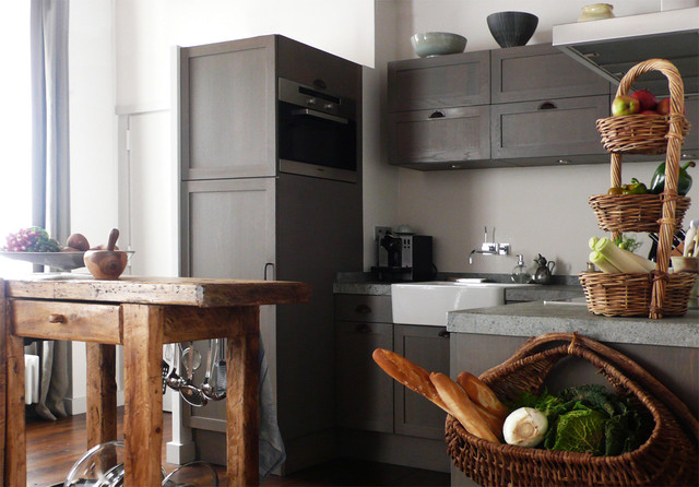This is an example of a large contemporary u-shaped kitchen/diner in Paris with a belfast sink, distressed cabinets, integrated appliances, dark hardwood flooring, an island and grey splashback.