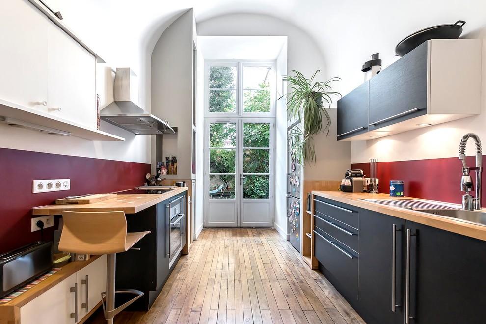 Exemple d'une grand cuisine parallèle et bicolore tendance fermée avec un évier posé, un placard à porte plane, des portes de placard noires, un plan de travail en bois, une crédence rouge, un sol en bois brun, aucun îlot et un électroménager en acier inoxydable.