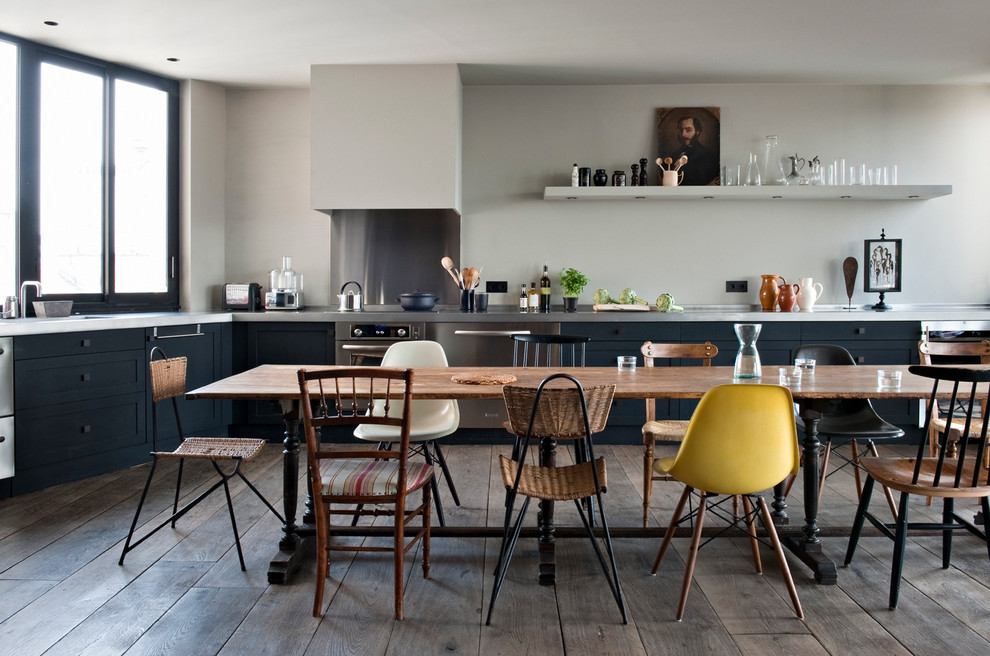 Example of a large urban l-shaped dark wood floor open concept kitchen design in Paris with black cabinets, stainless steel countertops, metallic backsplash, metal backsplash, stainless steel appliances and no island