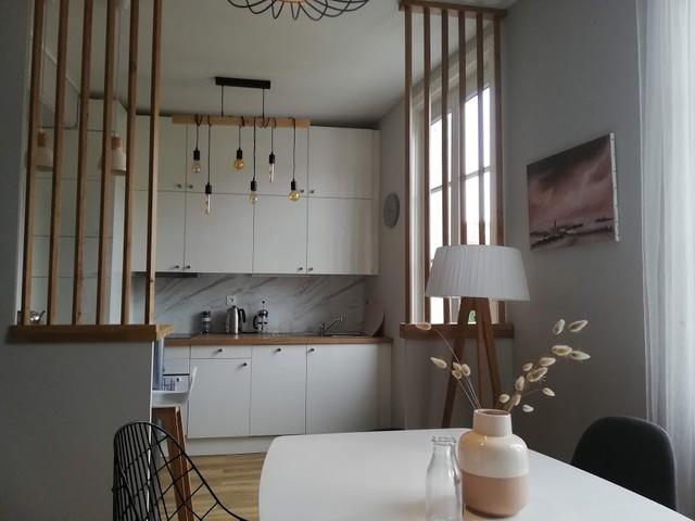 Modelo de cocina comedor de galera, nórdica, de tamaño medio, con armarios con rebordes decorativos, puertas de armario blancas, encimera de madera, salpicadero blanco, electrodomésticos de acero inoxidable, suelo de madera clara, una isla y encimeras marrones