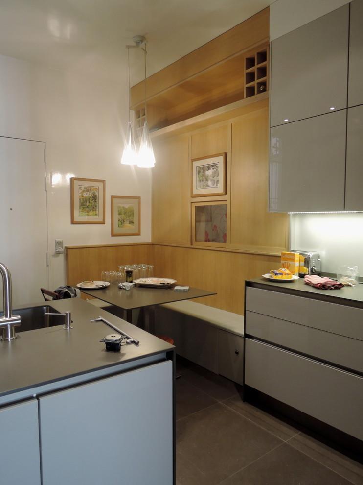 Cette image montre une grande cuisine linéaire design fermée avec un évier intégré, un placard à porte affleurante, des portes de placard grises, un plan de travail en surface solide et un îlot central.