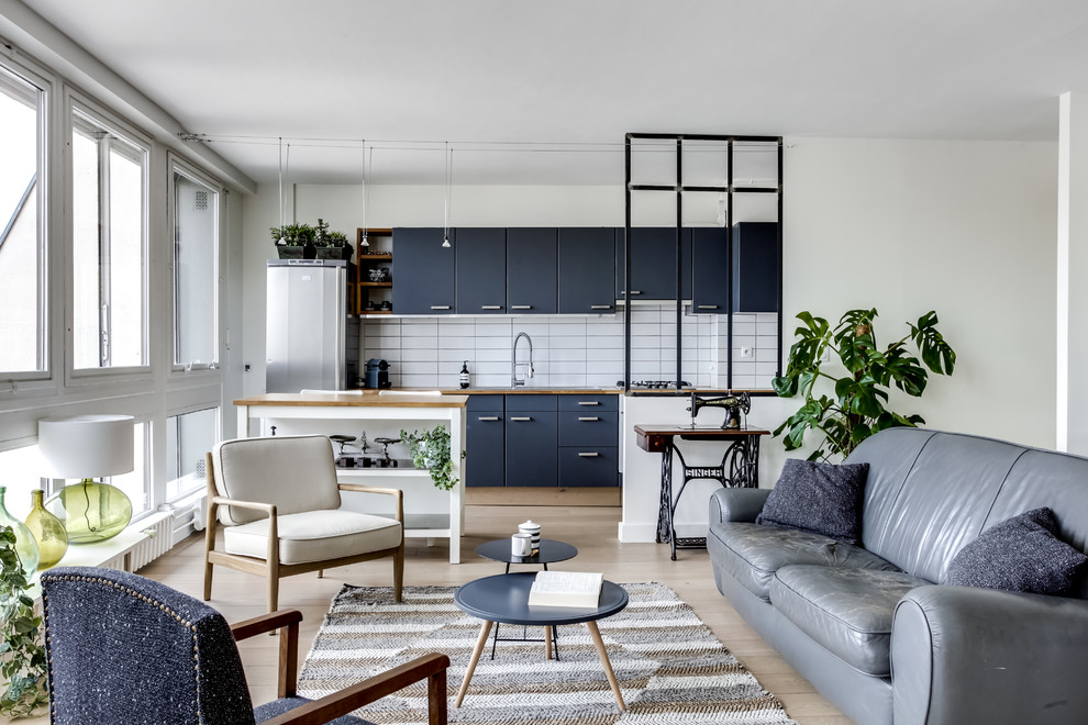 Example of a danish single-wall light wood floor and beige floor open concept kitchen design in Paris with flat-panel cabinets, blue cabinets, wood countertops, white backsplash, subway tile backsplash, stainless steel appliances and an island
