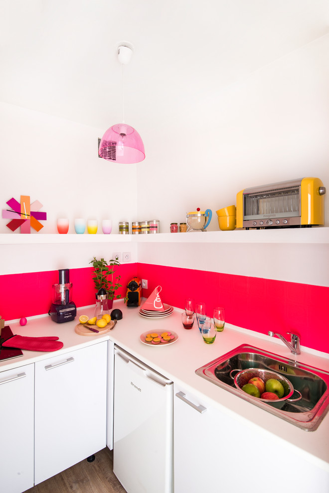 Small trendy l-shaped dark wood floor enclosed kitchen photo in Paris with a drop-in sink, flat-panel cabinets, white cabinets, pink backsplash, white appliances and no island
