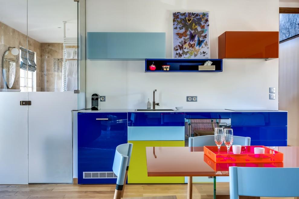Ispirazione per una cucina design di medie dimensioni con ante lisce, parquet chiaro, ante blu e nessuna isola