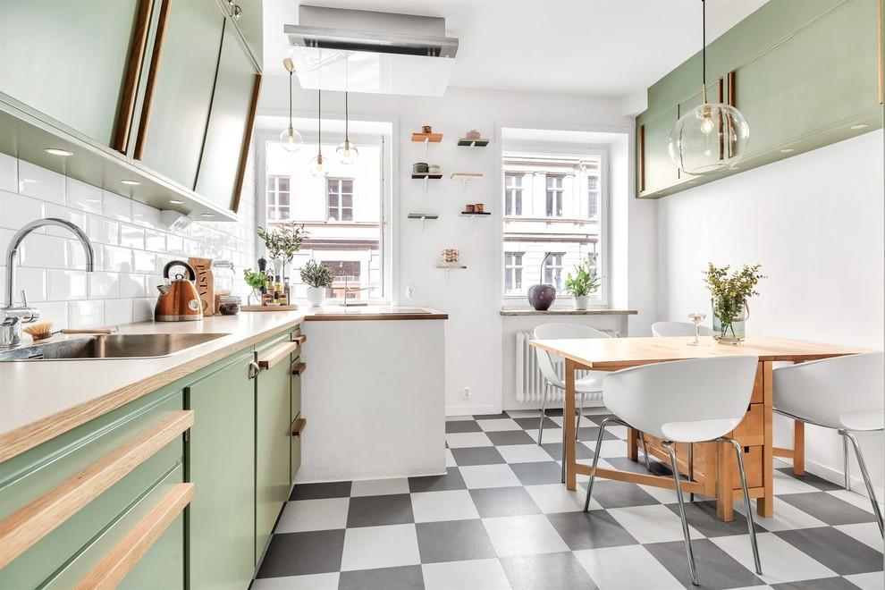 Idéer för ett 50 tals beige linjärt kök och matrum, med en nedsänkt diskho, släta luckor, gröna skåp, träbänkskiva, vitt stänkskydd, stänkskydd i tunnelbanekakel, integrerade vitvaror och flerfärgat golv