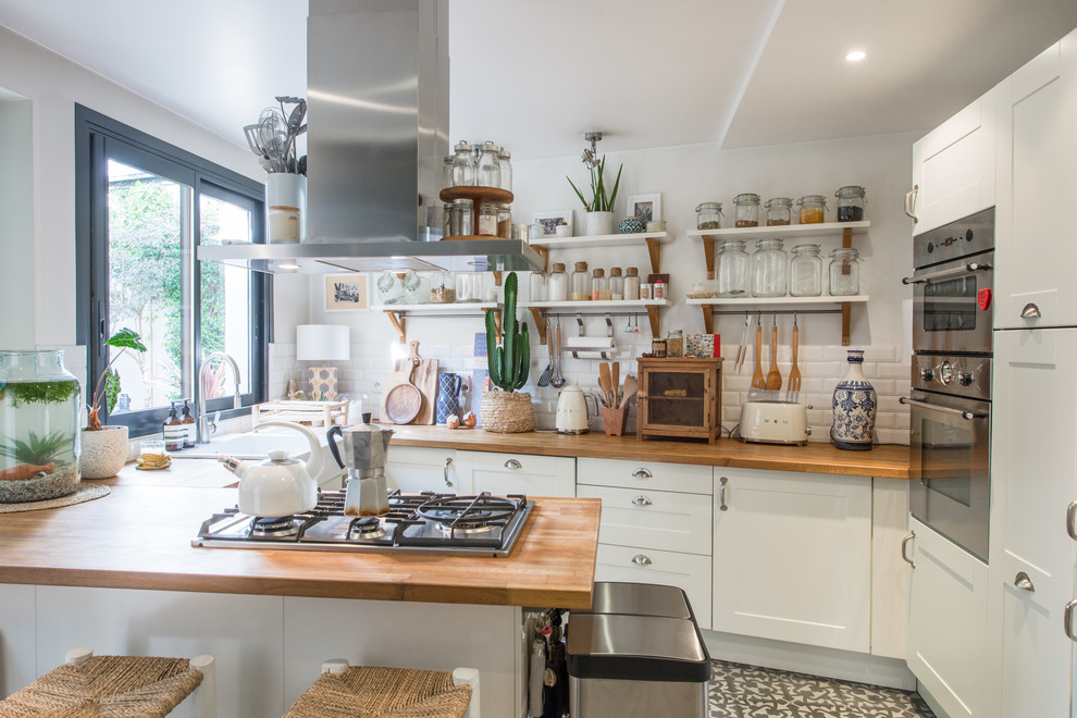 Example of an eclectic u-shaped gray floor kitchen design in Paris with a farmhouse sink, shaker cabinets, white cabinets, wood countertops, white backsplash, subway tile backsplash, stainless steel appliances and a peninsula