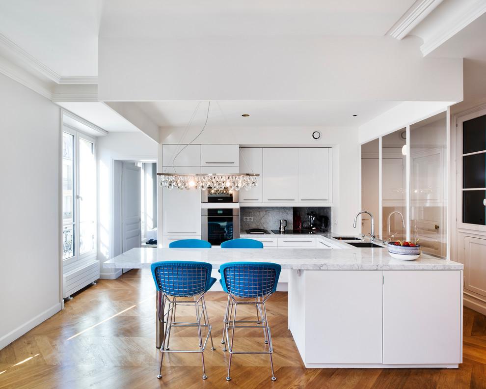 Aménagement d'une grande cuisine ouverte contemporaine en U avec un évier encastré, un placard à porte plane, des portes de placard blanches, un plan de travail en marbre, un électroménager en acier inoxydable, un sol en bois clair et une péninsule.
