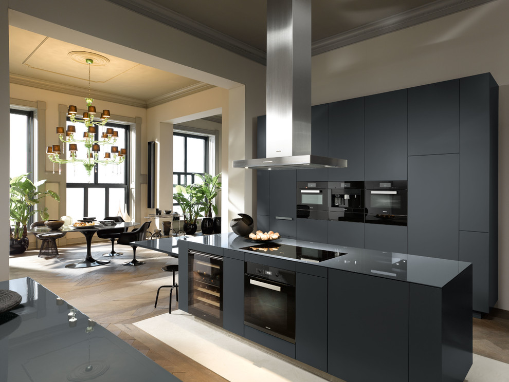 Open concept kitchen - large contemporary galley medium tone wood floor open concept kitchen idea in Oxfordshire with black cabinets, black appliances and an island