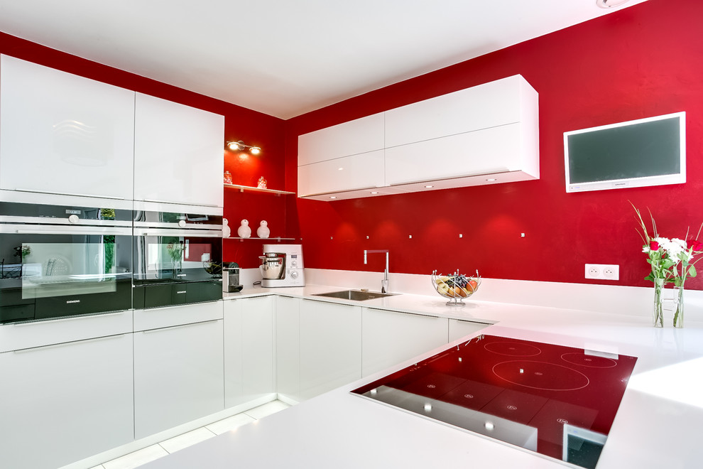 Example of a trendy u-shaped eat-in kitchen design in Paris with an undermount sink, flat-panel cabinets, white cabinets, red backsplash and white appliances