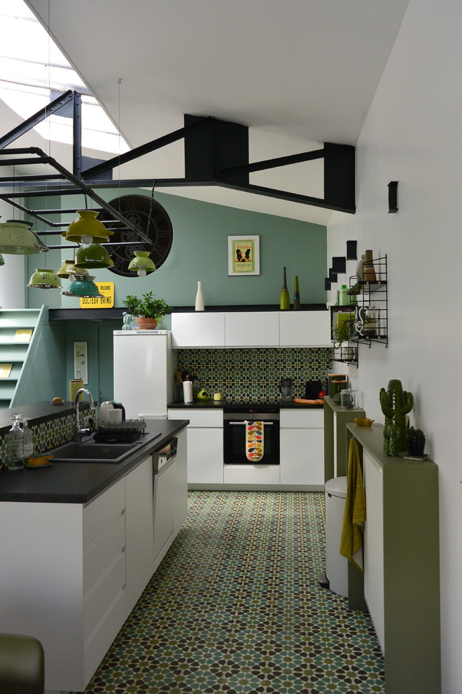 Inspiration for an eclectic l-shaped green floor open concept kitchen remodel in Paris with a drop-in sink, flat-panel cabinets, white cabinets, green backsplash, white appliances and an island