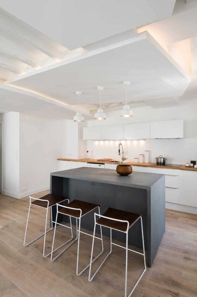 Idee per una cucina scandinava di medie dimensioni con ante lisce, ante bianche, parquet chiaro e isola