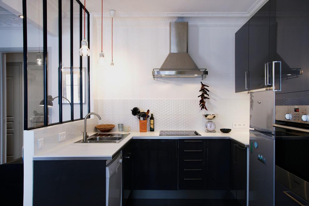Immagine di una cucina a U scandinava di medie dimensioni e chiusa con ante lisce, paraspruzzi bianco, nessuna isola, lavello da incasso, ante nere e elettrodomestici da incasso