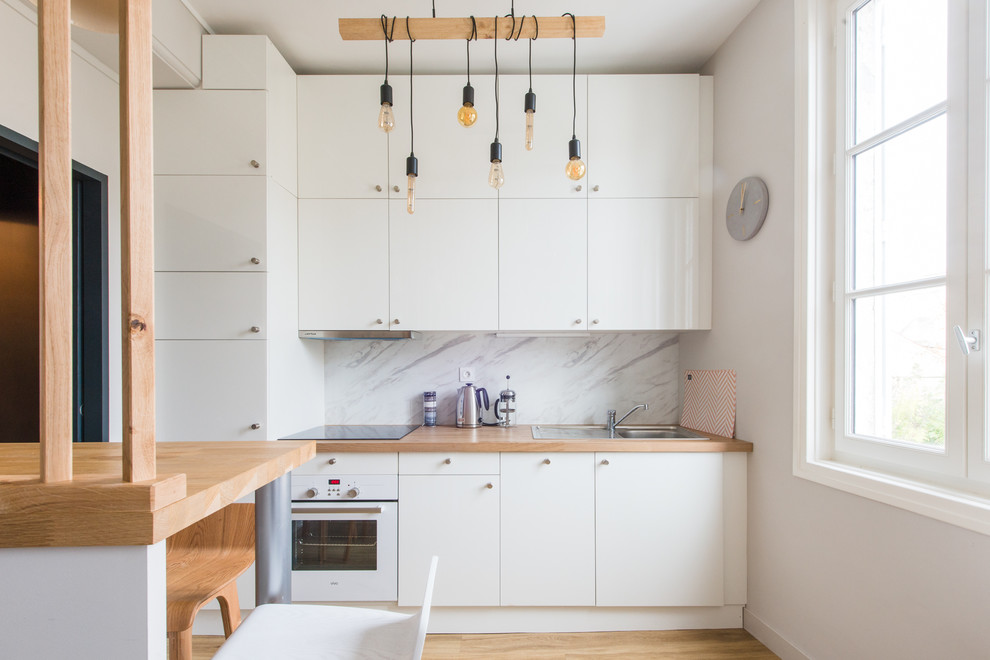 Inspiration for a scandinavian light wood floor and beige floor kitchen remodel in Montpellier with a drop-in sink, flat-panel cabinets, white cabinets, wood countertops, white backsplash, marble backsplash and white appliances