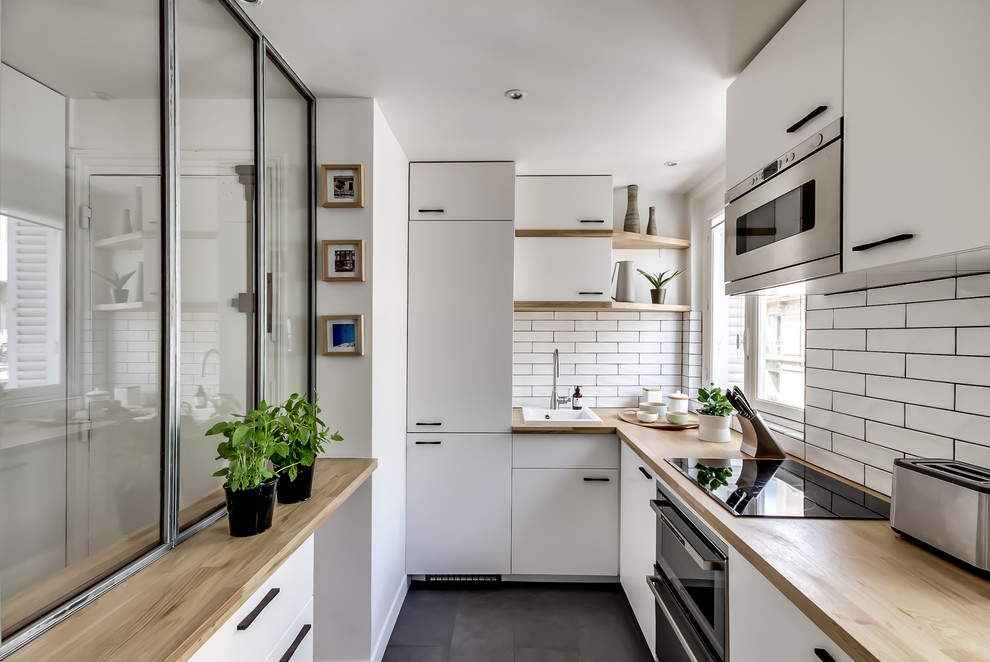 Example of a mid-sized danish u-shaped slate floor enclosed kitchen design in Paris with a drop-in sink, flat-panel cabinets, white cabinets, wood countertops, white backsplash, subway tile backsplash, paneled appliances and no island