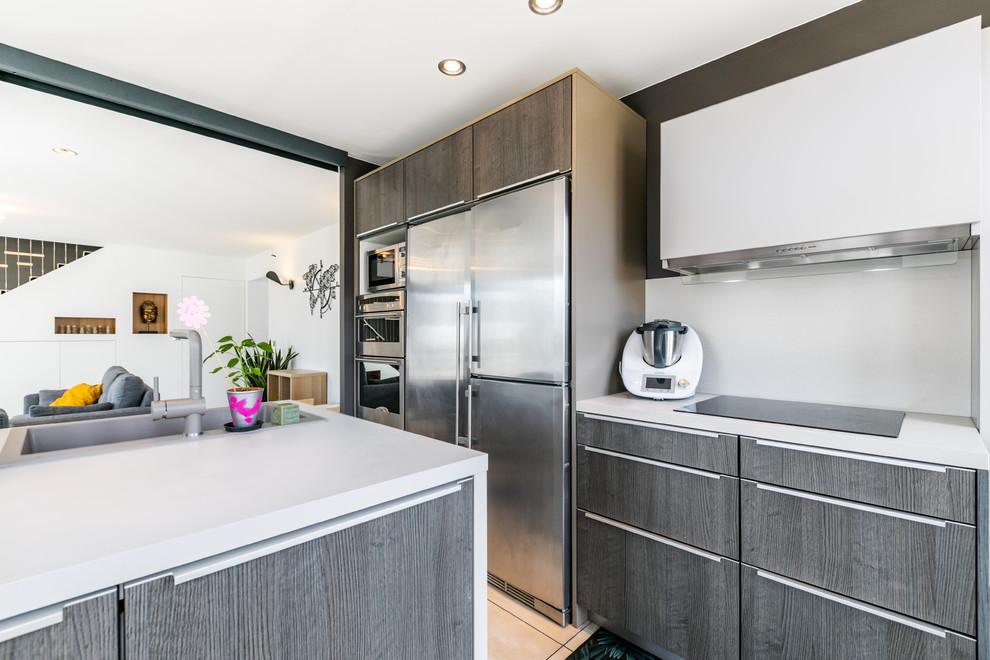 Cette photo montre une grand cuisine ouverte linéaire tendance avec un placard à porte affleurante, des portes de placard en bois sombre, un plan de travail en quartz, un électroménager en acier inoxydable, un sol en carrelage de céramique, un îlot central et un plan de travail blanc.