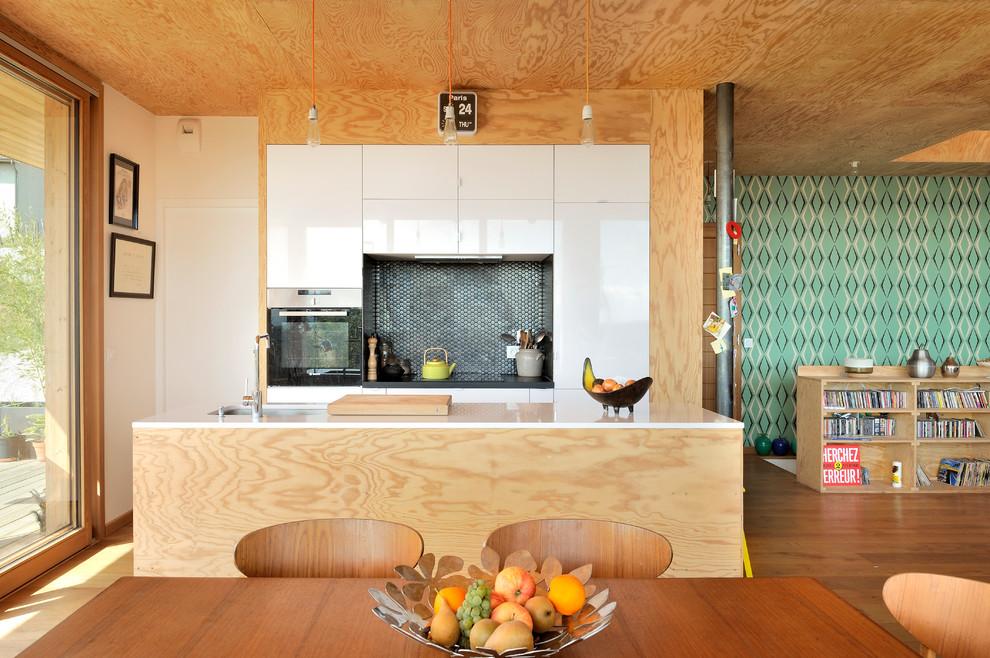 Idée de décoration pour une cuisine ouverte parallèle design de taille moyenne avec un évier encastré, des portes de placard blanches, une crédence grise, une crédence en mosaïque, un électroménager encastrable, un sol en bois brun et un îlot central.