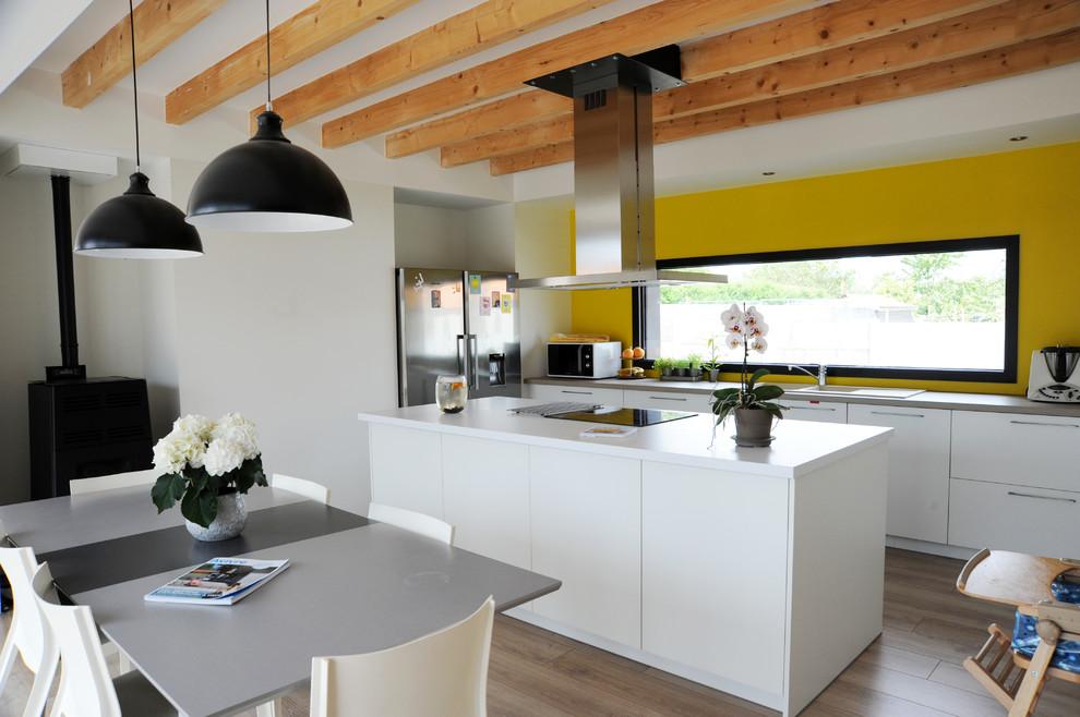 Idee per una grande cucina minimal con parquet chiaro e un'isola