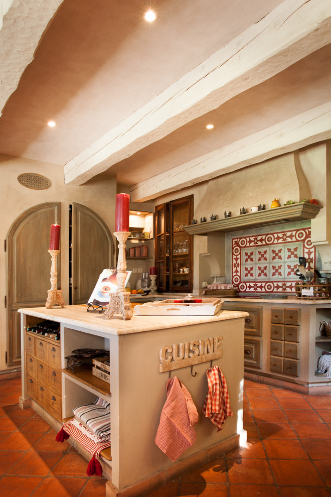 Example of a farmhouse galley enclosed kitchen design in Marseille with distressed cabinets and an island