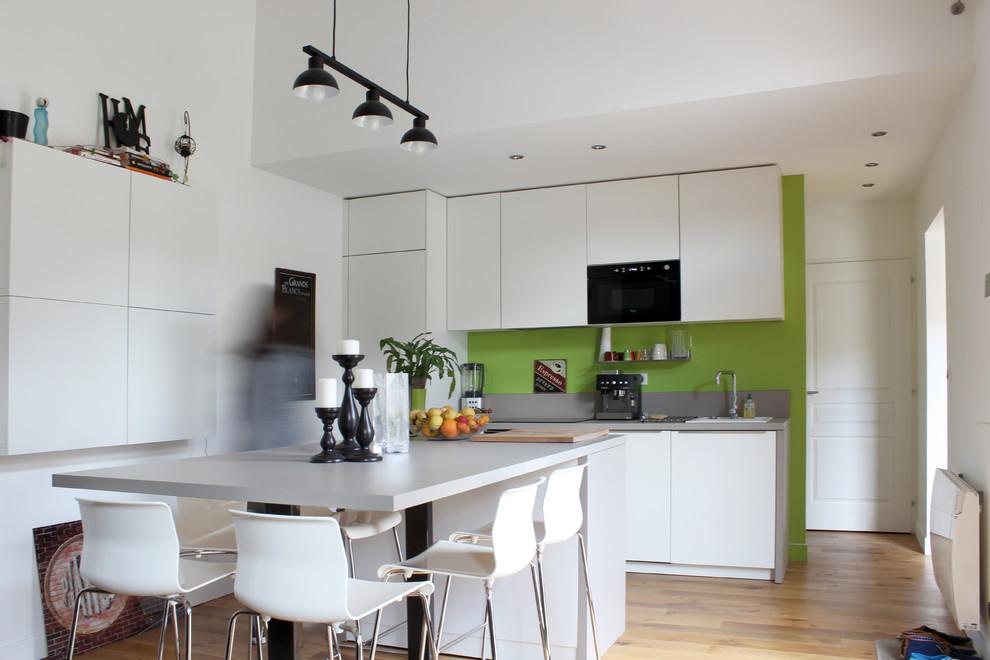 Modelo de cocina comedor lineal, actual, grande, con puertas de armario blancas, suelo de madera clara y una isla
