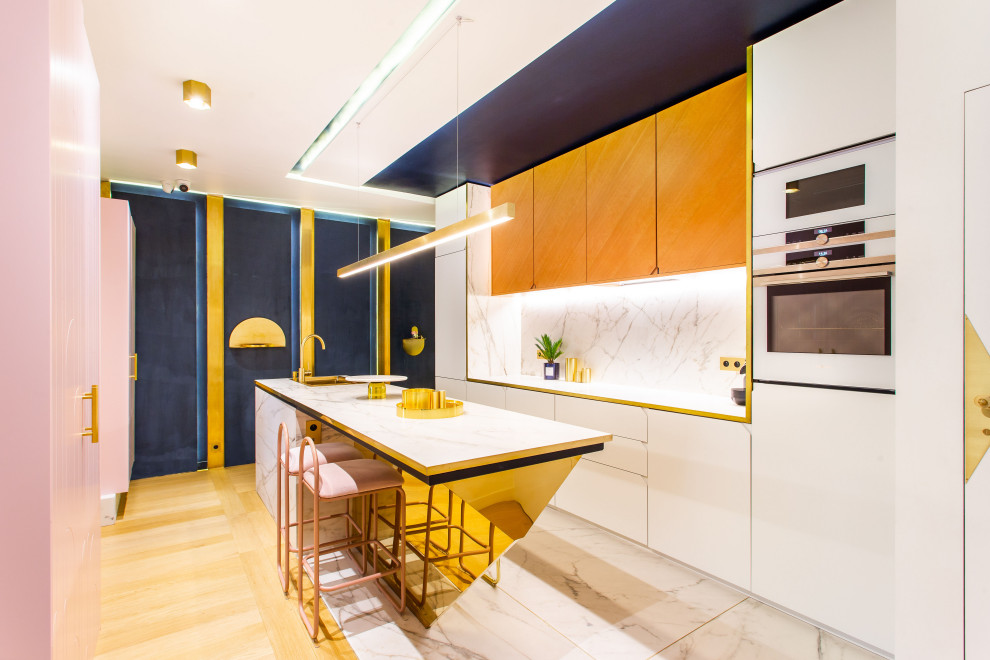 Example of a mid-sized trendy single-wall marble floor, white floor and tray ceiling open concept kitchen design in Paris with an integrated sink, beaded inset cabinets, light wood cabinets, marble countertops, white backsplash, marble backsplash, white appliances, an island and white countertops