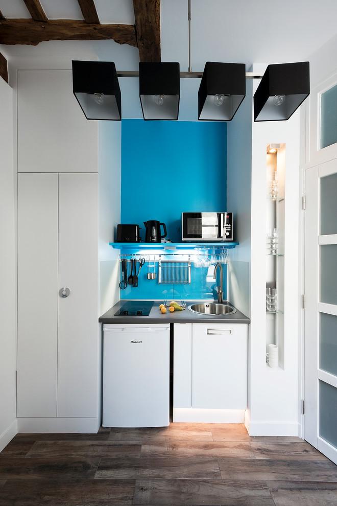 Aménagement d'une petite cuisine linéaire contemporaine fermée avec des portes de placard blanches et aucun îlot.