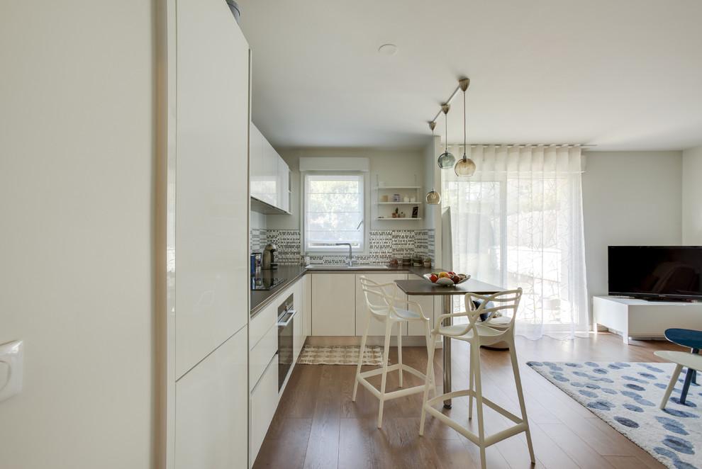 パリの小さいコノ字型コンテンポラリースタイルのダイニングキッチンの画像 (シングルシンク、シェーカースタイル扉のキャビネット、白いキャビネット、ラミネートカウンター、ベージュキッチンパネル、セラミックタイルのキッチンパネル、パネルと同色の調理設備、ラミネートの床、アイランド1つ、茶色い床、茶色いキッチンカウンター)